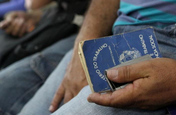Aparece mão de um trabalhador segurando carteira de trabalho